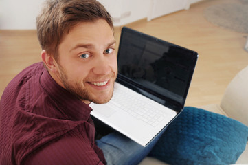 portrait of attractive young man with laptop on the sofa at home