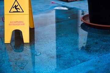 Achtung Rutschgefahr - Gefahrenschild auf nassem Fußboden