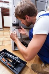 Man repairing fridge at home