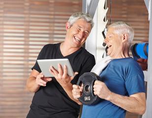 Senioren trainieren mit Tablet PC im Fitnesscenter