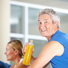 Älterer Mann trinkt Sportgetränk
