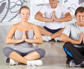 Gruppe Senioren bei Meditation im Fitnesscenter