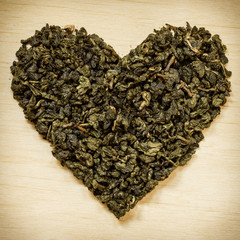 Green tea leaves heart shaped on wooden surface