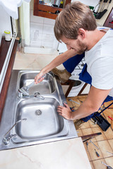 Young man repairing kitchen sink