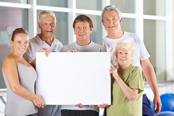 Senioren halten leeres Schild im Fitnesscenter