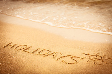 The word holidays written in the sand on a beach