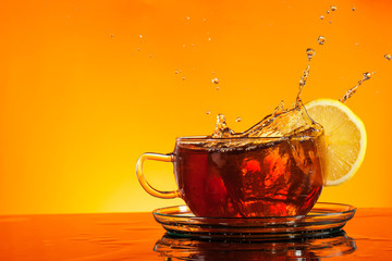 Tea splashing out of glass with orange background