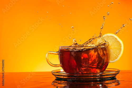 Tuinposter Thee Tea splashing out of glass with orange background
