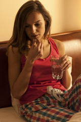 Woman sipping sleeping pills with water