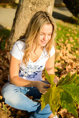 Girl sitting in the autumn leaves