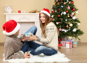Young couple with gifts, sitting on carpet, at home
