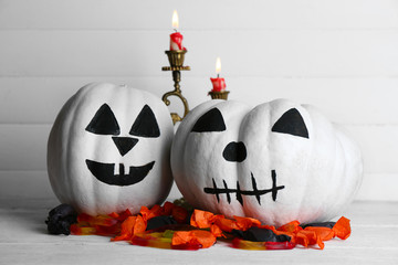 White Halloween pumpkins, candles and candies,