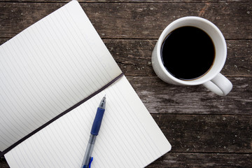 image of coffee cup with notebook and pen on an old wooden table