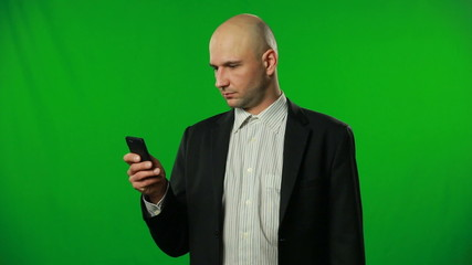 Handsome businessman texting on green background.FULL HD.