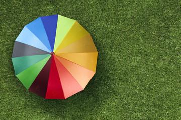 Turkish Lira currency units on colourful umbrella on green grass