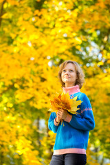Young girl with bunch of maple leaves