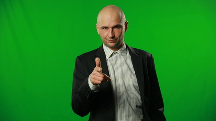 Handsome buisnessman pointing YOU on a green background.FULL HD.