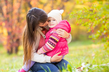 beautiful mother embracing kid girl outdoors in fall