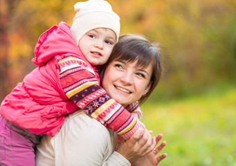 happy mother with kid girl outdoor in autumn park