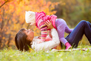 happy woman and daughter child play outdoors in fall