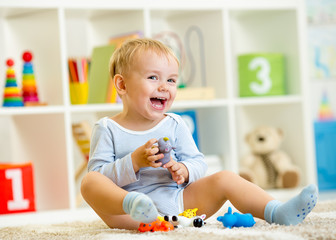 kid playing with toy animals indoors