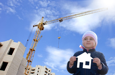 Happy little girl with paper house in hands.Construction