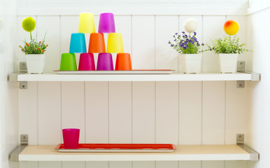 Plastic color cup on white shelf