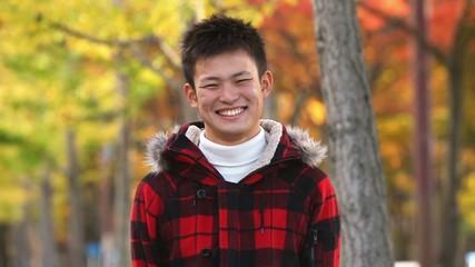 紅葉のなかで笑顔の男性_2