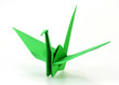 Traditional Japanese origami crane made of green paper over whit