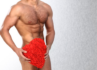 Photo of naked athlete man with strong body, with big red heart