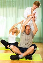 Yoga instructor showing asana to mature couple