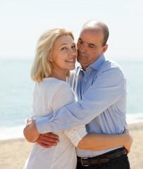 Happy couple at sea vacation smiling and hug