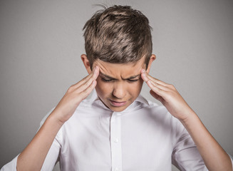Stressed teenager boy with headache on grey background