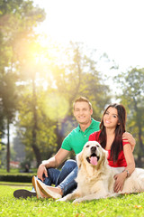 Couple posing in a park with their dog