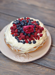on a wooden dish with white background cake with raspberries