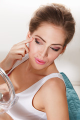 Beautiful woman checking her makeup in the mirror