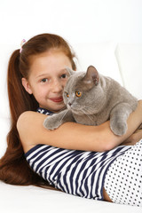 Beautiful little girl with cat on sofa in room