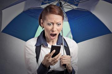 shocked woman reading news on smartphone holding umbrella