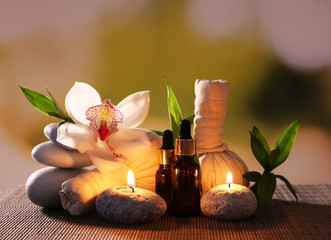 Spa composition with herbal massage bags, candles and bamboo