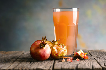 Glass of pomegranate juice on wooden