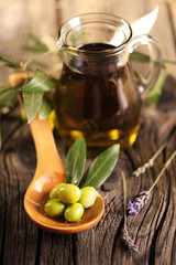 A jar of olive oil and a wooden spoon with olives on a table