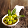 canvas print picture - Green olives in the bowl and olive branch on wooden table
