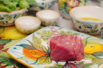 raw tuna fillet with vegetables in the background