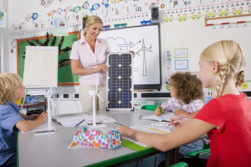 Teacher explaining solar panel to students in school classroom