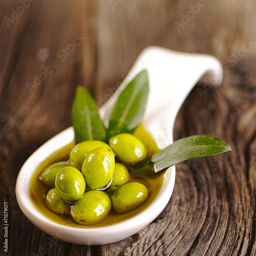 canvas print picture Green olives in the bowl and olive branch on wooden table