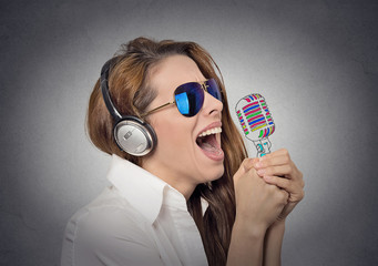 headshot woman with sunglasses singing with microphone