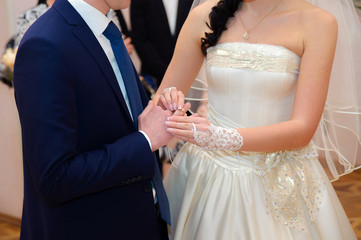 Bride putting a wedding ring on a groom's finger