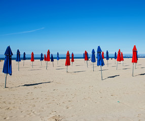 Red and blue umbrellas on the beach in Deauville