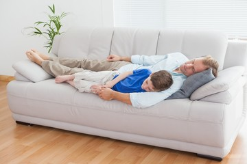 Father and son using napping on the couch