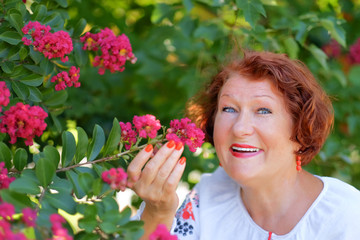 Mature  red haired woman  dressed in an embroidered blouse with